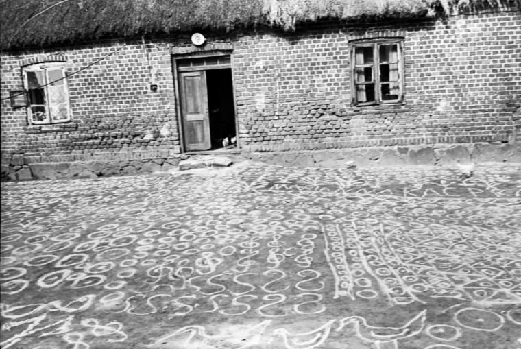 Drawing protective symbols with sand in Poland